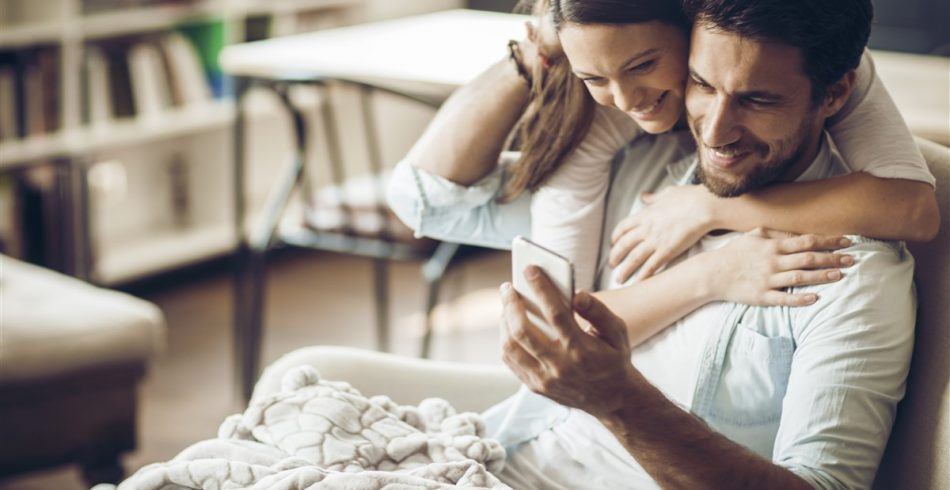 Couple_hugging_with_smartphone-950x490